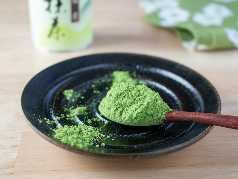 Ceremonial grade matcha on a wooden spoon over a black plate.