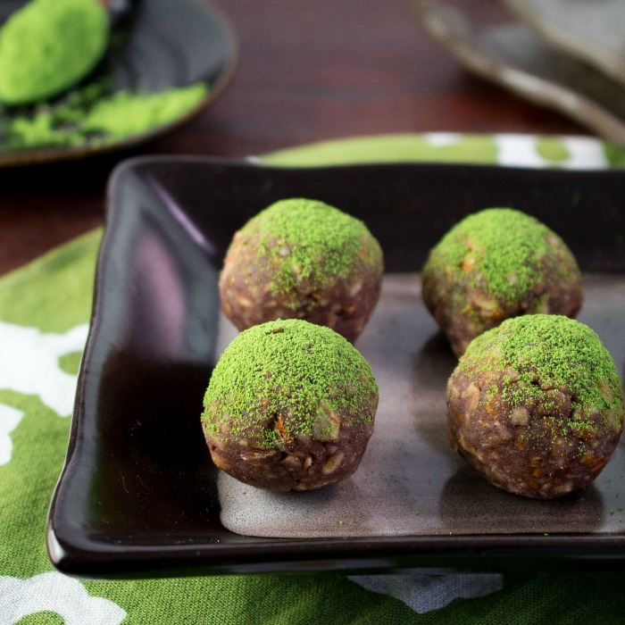 Matcha Red Bean Energy Balls all lined up in a row and the dusting of super bright green antioxidant rich green tea on top.