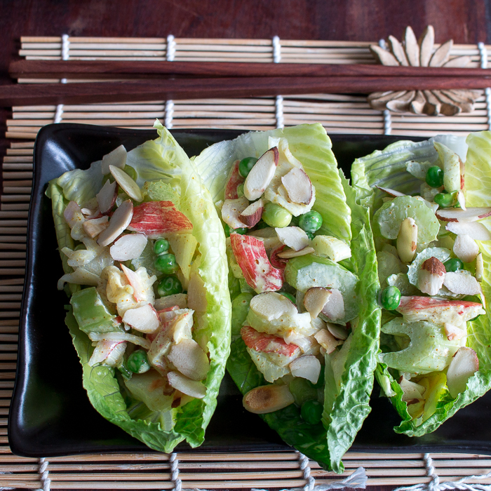 3 lettuce cups filled with crab salad on a black plate with chopsticks on a Japanese mat.