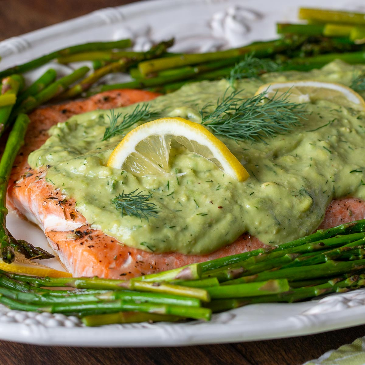 Baked salmon with avocado sauce on top with asparagus on a white serving platter.