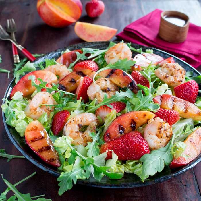 Delicious plate of salad with grilled shrimp, necatrines with dressing on the side.