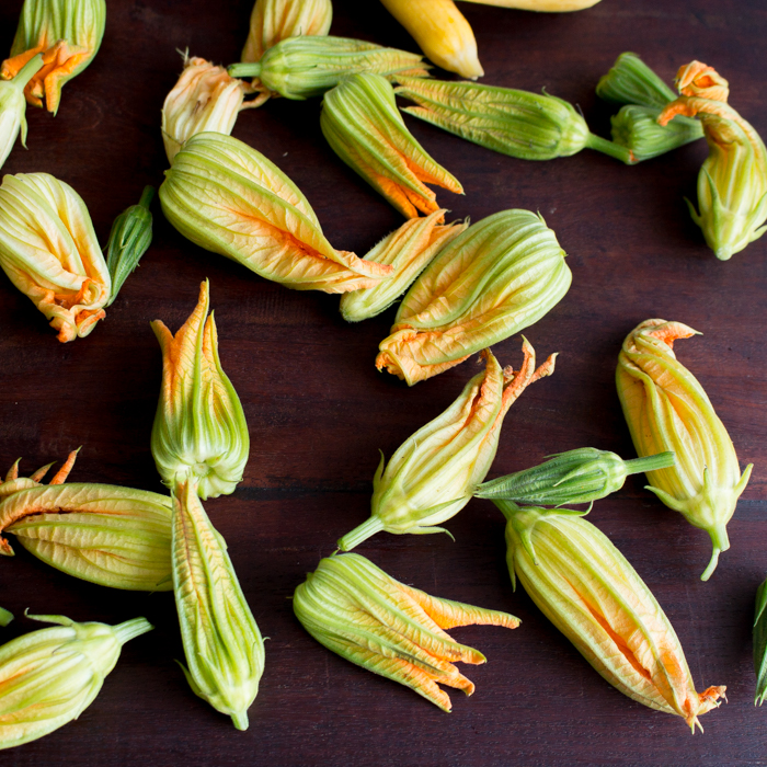 Fresh zucchini blossoms on a brown cutting board.