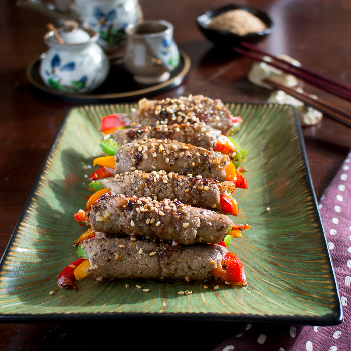 Beef wrapped around peppers on green plate