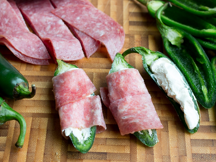 raw jalapeno stuffed with cream cheese getting wrapped with salami slices