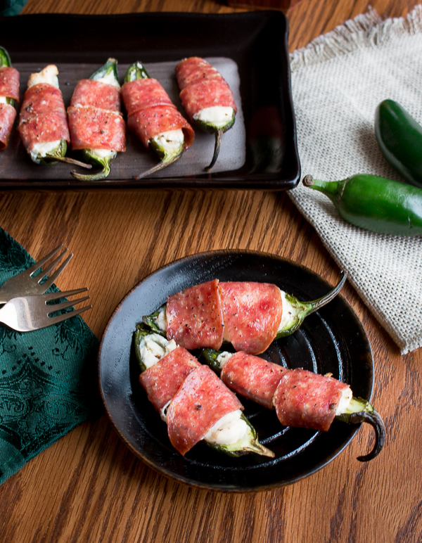 Long photo of Baked Cheesy Salami Wrapped Jalapeños in black serving dishes