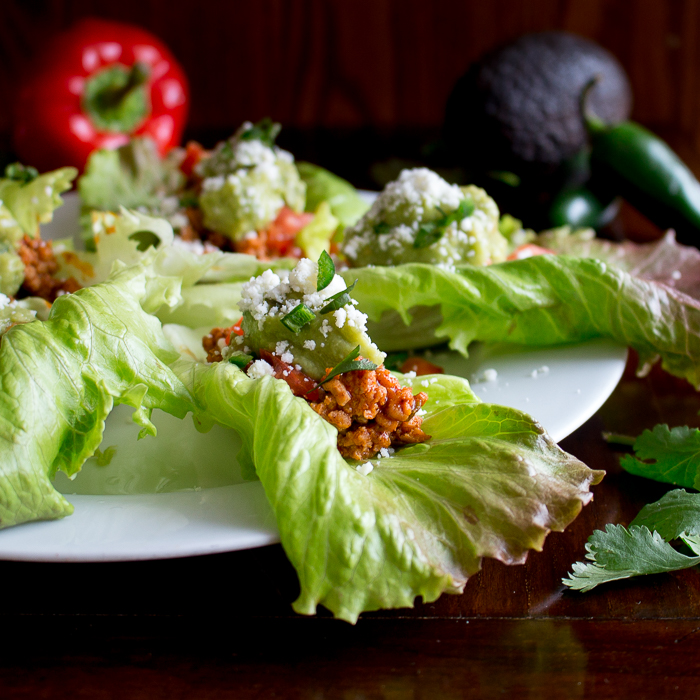 45 degree close up view of turkey lettuce wrap with avocado and red pepper props