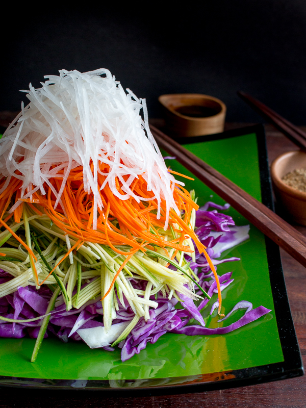 Mountain high layered Asian Salad with sesame seeds and tamari dressing on side with chopsticks