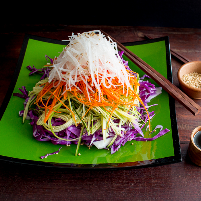 Layered Asian salad with sesame served with a side of tamari ginger dressing and sesame seeds