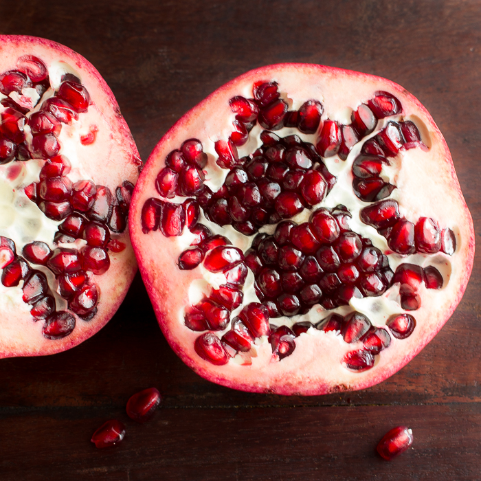pomegranate cut in half with red ruby seeds