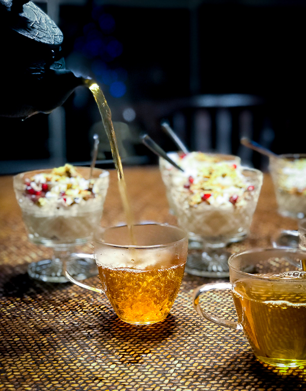 Healthy Moroccan Mint Tea being poured high into cups with desserts on table