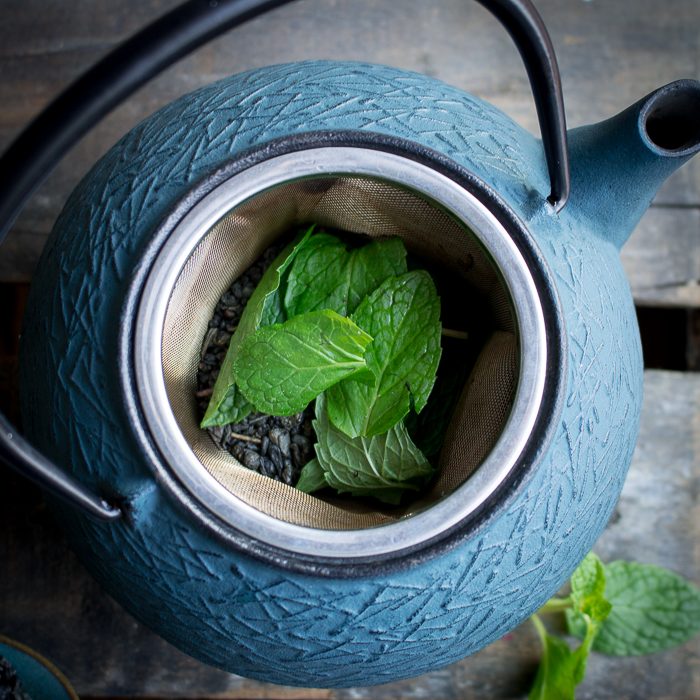 Top down shot looking into tea pot with gunpowder tea and mint leaves