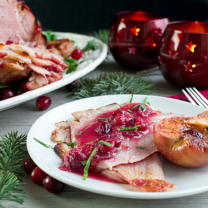 Sliced holiday ham topped with extra cranberry sauce