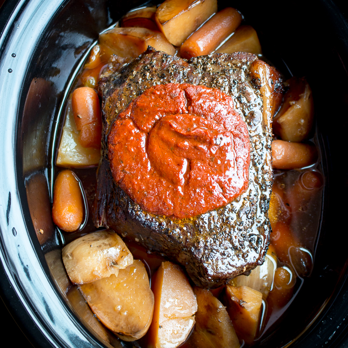 The whole cooked beef roast in the slow cooker with tomato sauce on top.