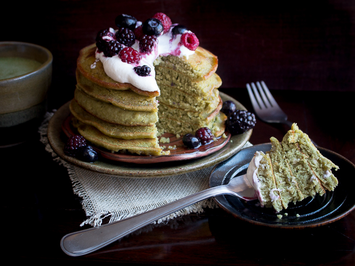 Matcha pancakes are slices showing the bite shot on a fork on a black plate.