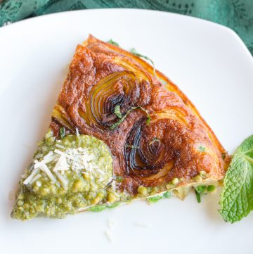 Stove Top Parmesan Leek Frittata slice on a shite plate with a dollop of pesto on top.