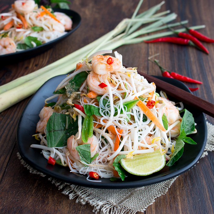 Vietnamese Shrimp Vermicelli Salad stacked high on a black plate with lemon grass and chili peppers scattered around the plate.