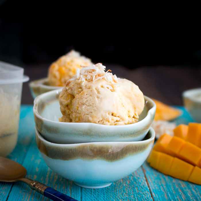 Single large scoop of the mango ice cream in a blue bowl.