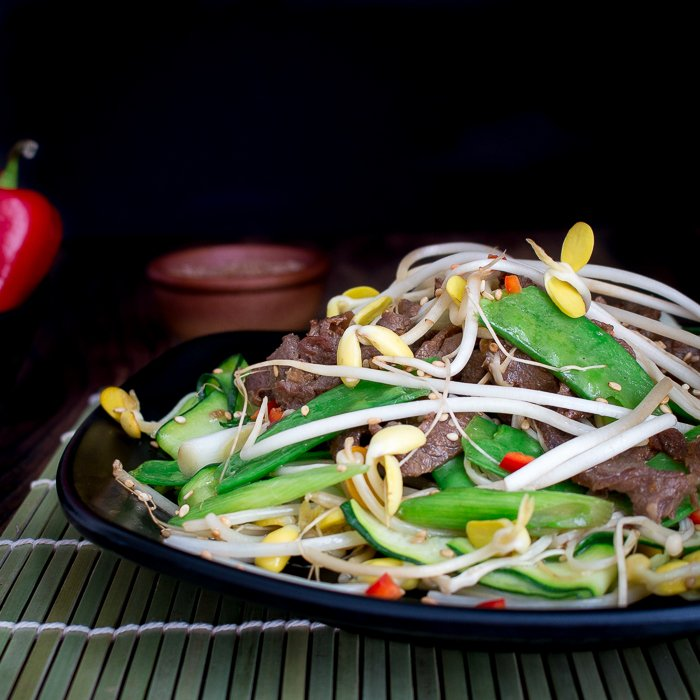 Beef and vegetable stir fried on a black serving plate with a green placemat underneath.