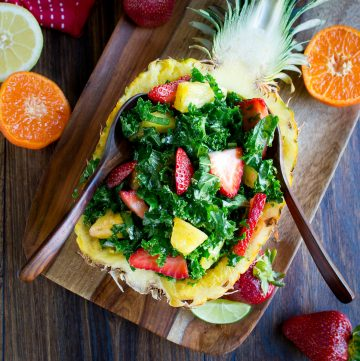 Tutti Fruitti Kale Salad and Citrus Honey Dressing in a 1/2 pineapple with wooden spoons and fruit around on a wooden board.