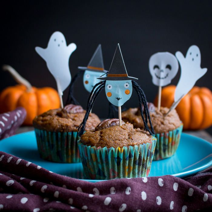 Muffins adorned with fun Halloween characters on little sticks.