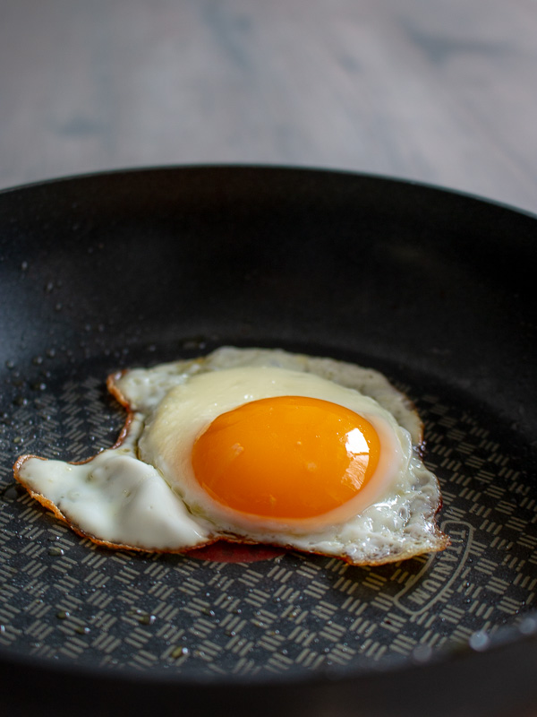 Perfectly cooked sunny side up egg in a frying pan.
