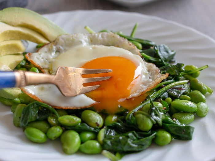 Bite shot. Fork poking a hole into the sunny side up egg.
