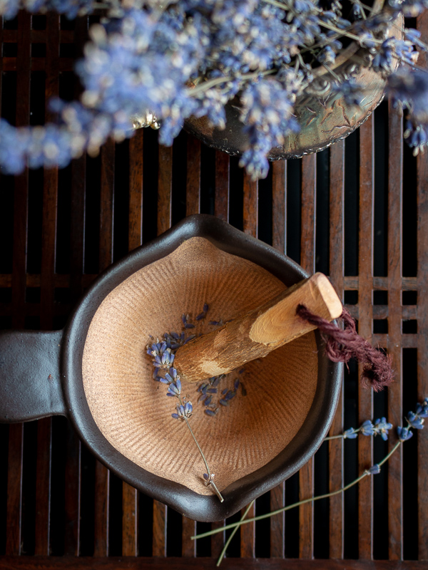 Lavender being crushed in a mortar and pestle.