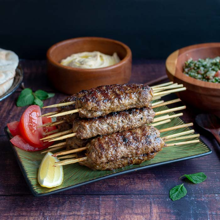 Delicious tray of grilled lamb kabobs garnished withe slices of lemons, tomatoes and pita breads and hummus in the background.