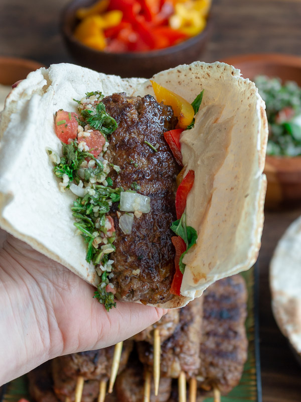 A lamb kabob held in a hand nestled in a pita bread with hummus, grilled peppers, tabbouleh and all the fixings.