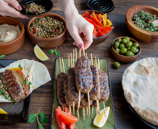 Person grabbing a lamb kabob off the entertaining table with all of the toppings for a Middle Eastern Party.