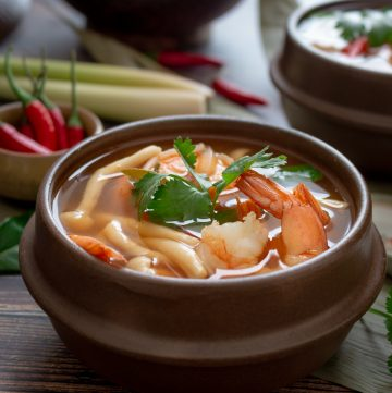 Delicious bowl of Thai Hot and Sour Prawn Shrimp in a brown rustic bowl garnished with fresh cilantro.
