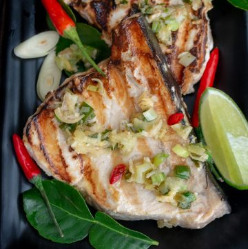 Tropical Thai Swordfish just hot off the grill, topped with lemongrass sauce and chilis, and limes on a black plate with perfect grill marks.