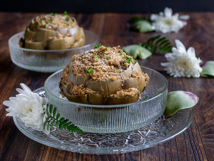 2 gigantic globe artichokes stuffed and steamed in glass bowls with white flowers around the bowls.