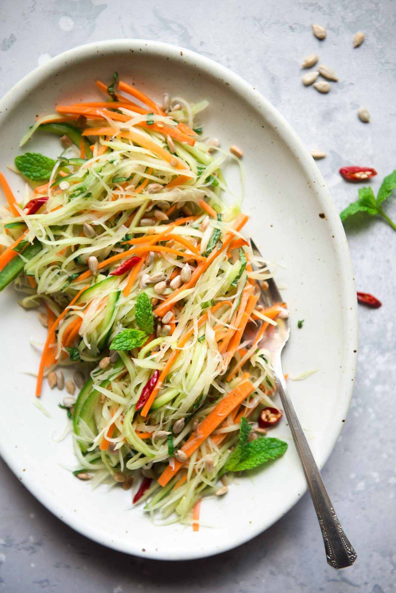 Vegan green papaya salad garnished with sunflower seeds, mint and chili