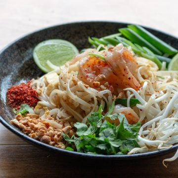 Bowl of delicious Pad Thai with all the fixings such as ground peanuts, chilis, green onions and limes on the side in a black bowl.
