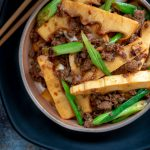 top down photo of stir fried spicy pork and fresh bamboo shoots with chopsticks