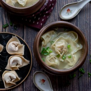 Shanghai Wonton Soup with a plate of wontons to be cooked next to it and 2 spoons.