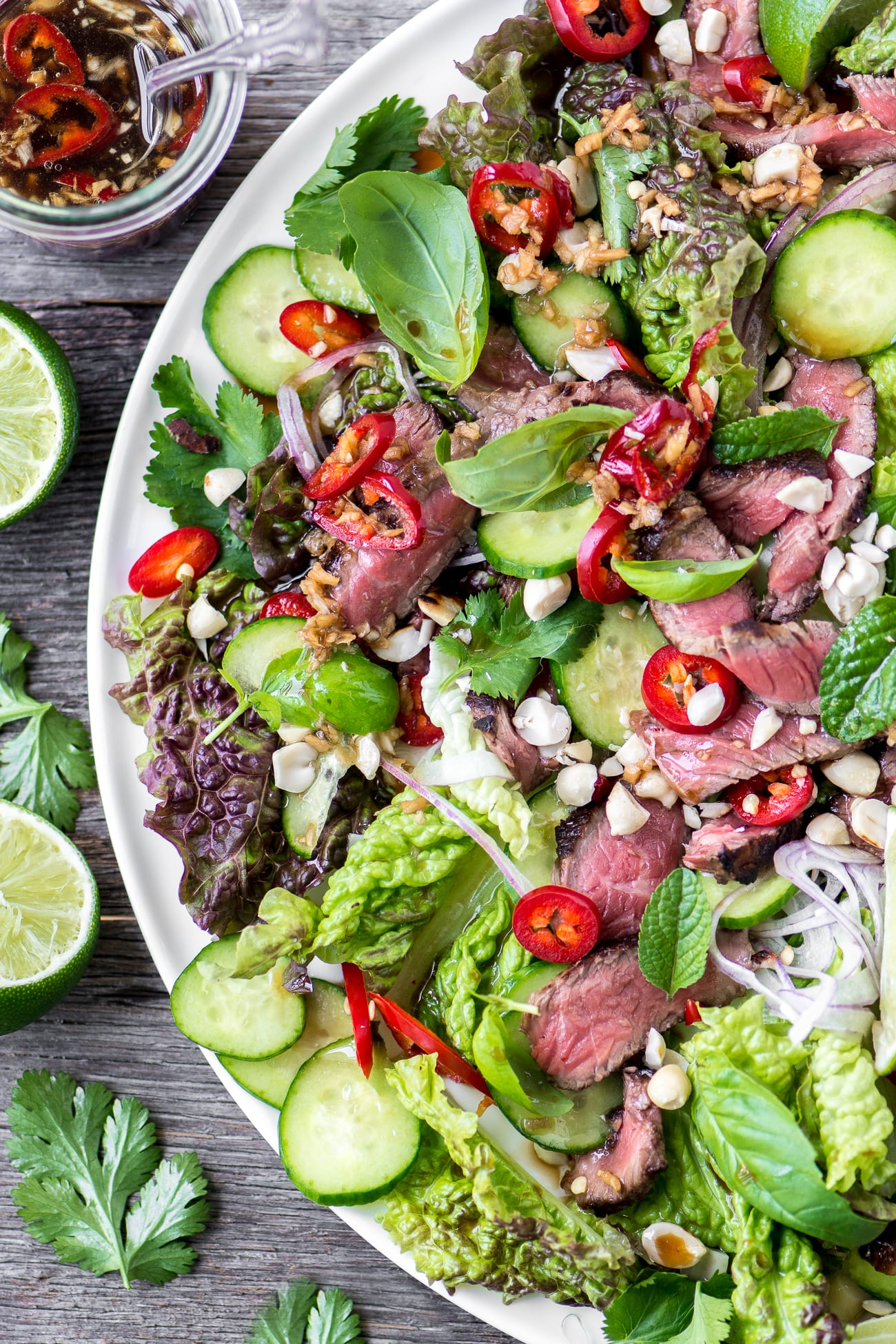 Thai Beef Salad garnished with chilis and limes