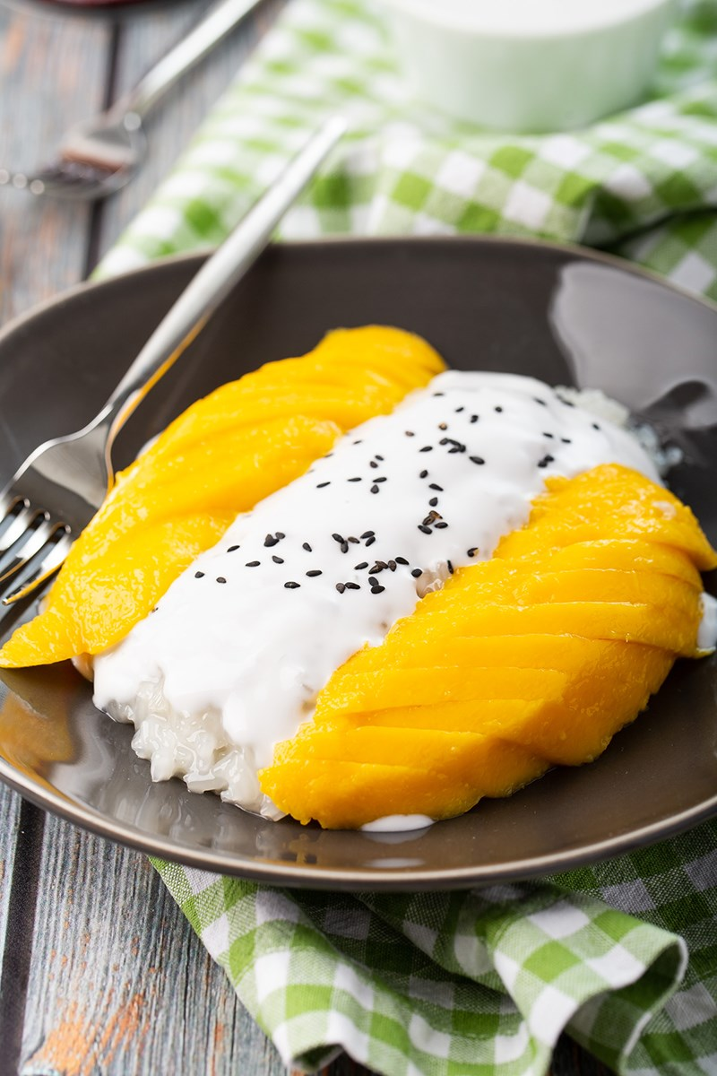 mango sticky rice with coconut cream on top of rice