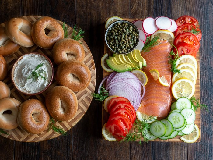 Round cutting board with bagels and cream cheese on the left and on the right a rectangle cutting board packed with lox, tomatoes, cucumbers, capers, lemons dills, radishes and onions.