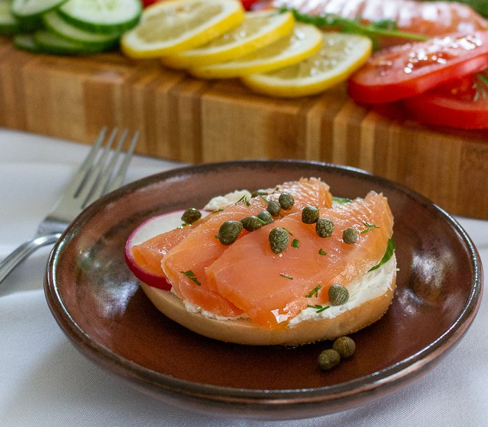 Bagel with cream cheese, lox, radish, cucumber, capers and a little dill on top.