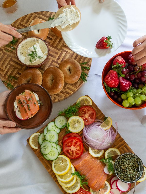 Friends gathering around the Ultimate Bagel brunch board and digging in.