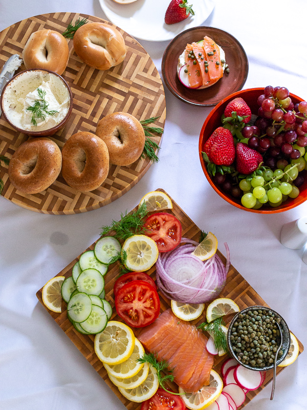 Top down shot of bagel bar with assembled bagels and a bowl of seasonal berries and grapes.