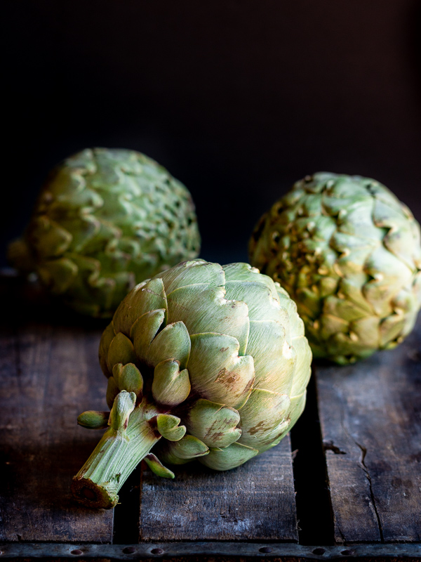 3 extra large globe artichokes on a dark wooden box with the stem facing towards you. They are whole and just home from the farmers market.