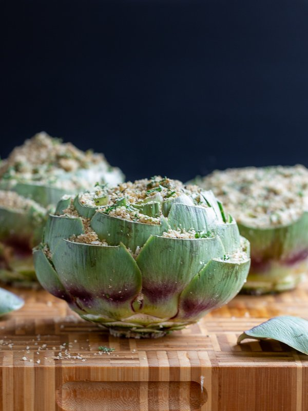 3 artichokes stuffed on a bamboo cutting board ready to be steamed.
