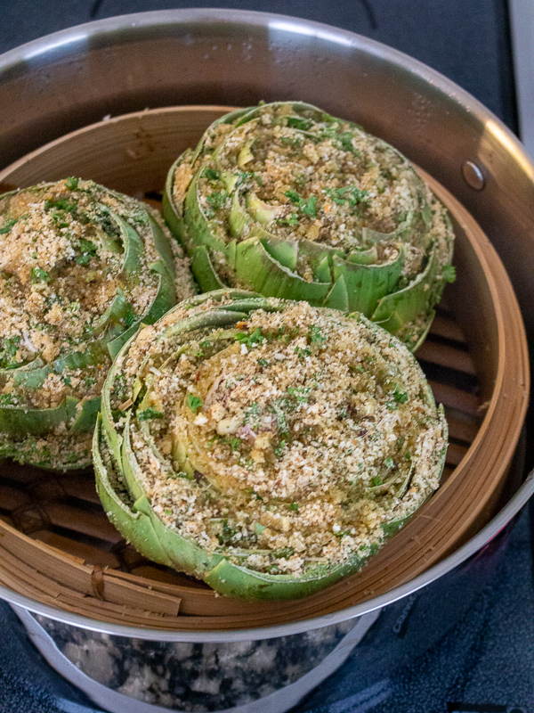 3 steamed and cooked artichokes in a bamboo steamer basket.