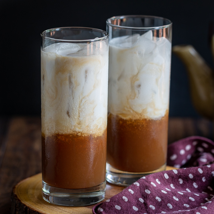 Two glasses of Easy Coconut Iced chai Tea that show the tea at the bottom and the coconut milk just poured on the top and swirls that it is starting to mix with the ice.