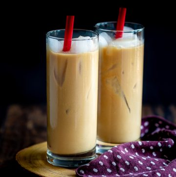 Two glasses of Easy Coconut Iced Chai Tea Latte with red straws and lots of ice on a wooden board with a polka dot napkin.