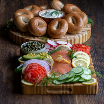 DIY Ultimate Bagel Bar Brunch on a cutting board with lox, cream cheese, vegetables and all the fixings and a platter of bagels.