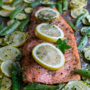 Lemon Herb Baked Rainbow Trout on a sheetpan hot out of the oven with fresh lemon slices and herbs on top.